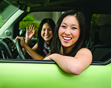 Two women smiling in green car