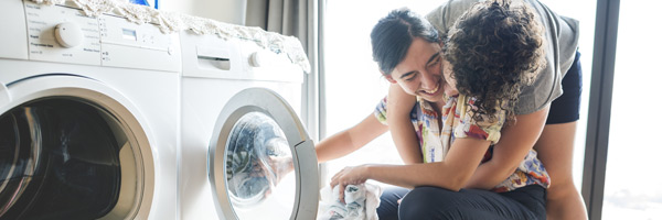 Two women embrace next to clothes dryer at home