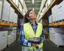 Woman holding scanner works in warehouse