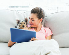 Smiling woman reads tablet on couch with her dog
