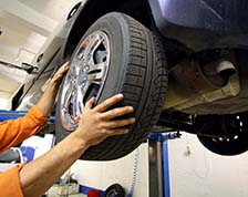 man installs a tire on a car in a body shop
