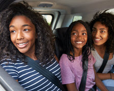Kids in back seat smiling out the window of moving car