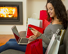 Woman shops for holiday gifts at home using her computer
