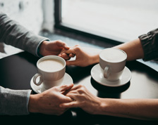 Two people hold hands next to coffee cups at a cafe