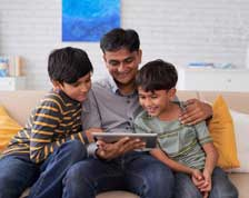 Father and sons look at tablet computer while at home