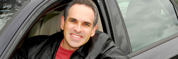 Man smiles from driver seat of rental car