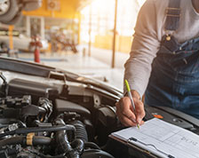 Auto mechanic inspects engine and marks checklist