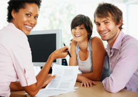 Female insurance agent sitting with two customers discussing a policy