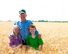 Grandfather stands in his wheat field with two young grandchildren
