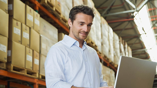 man in warehouse on computer