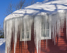 Red building with snow covered roof and long icicles hanging from its gutters