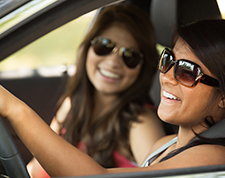 Two teenage girls chat while driving