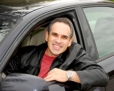 Man smiles and looks out window while driving a rental car