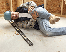 Construction worker holds his knee after falling